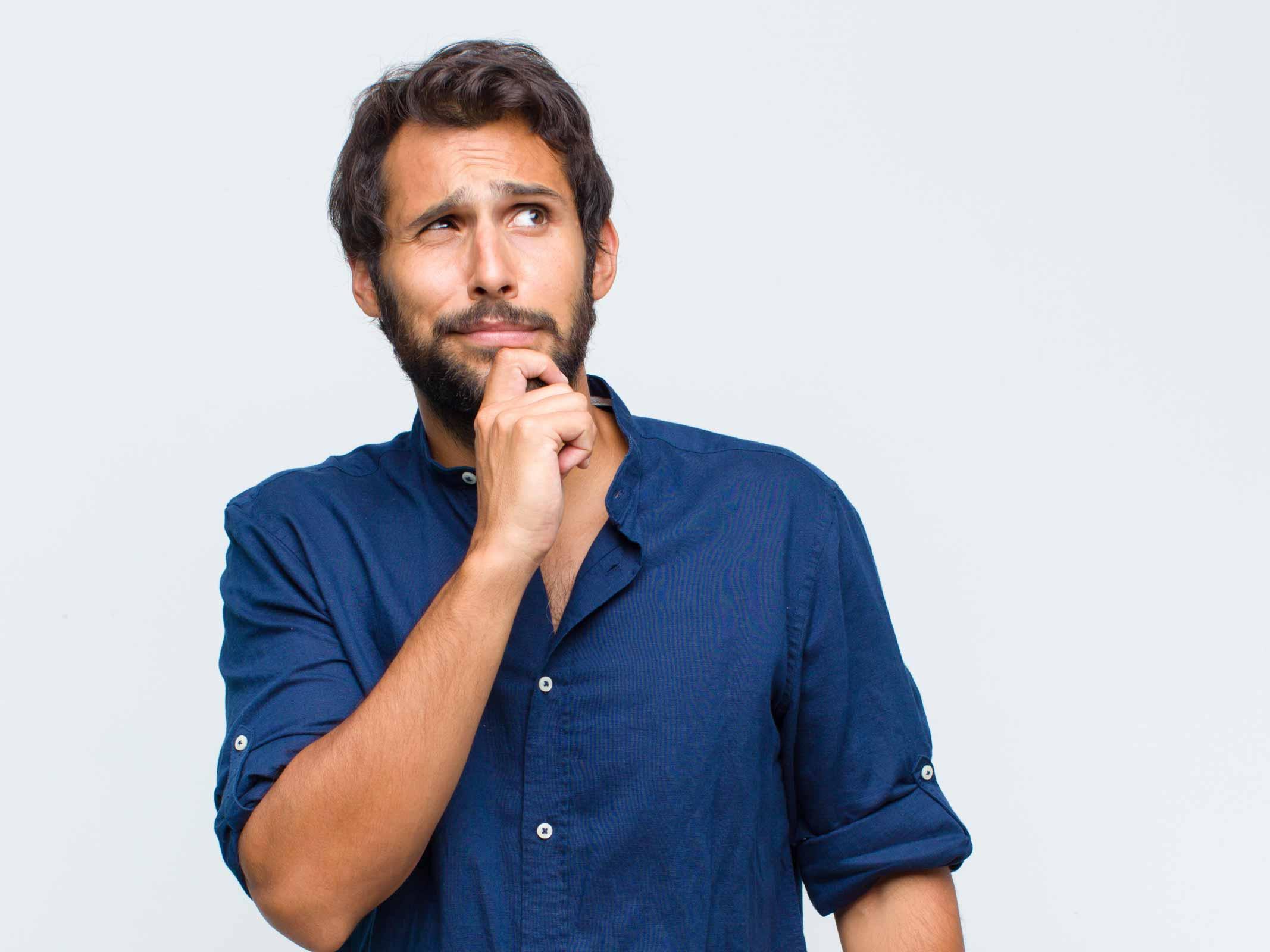 homme brun avec barbe qui se tient le menton en réfléchissant