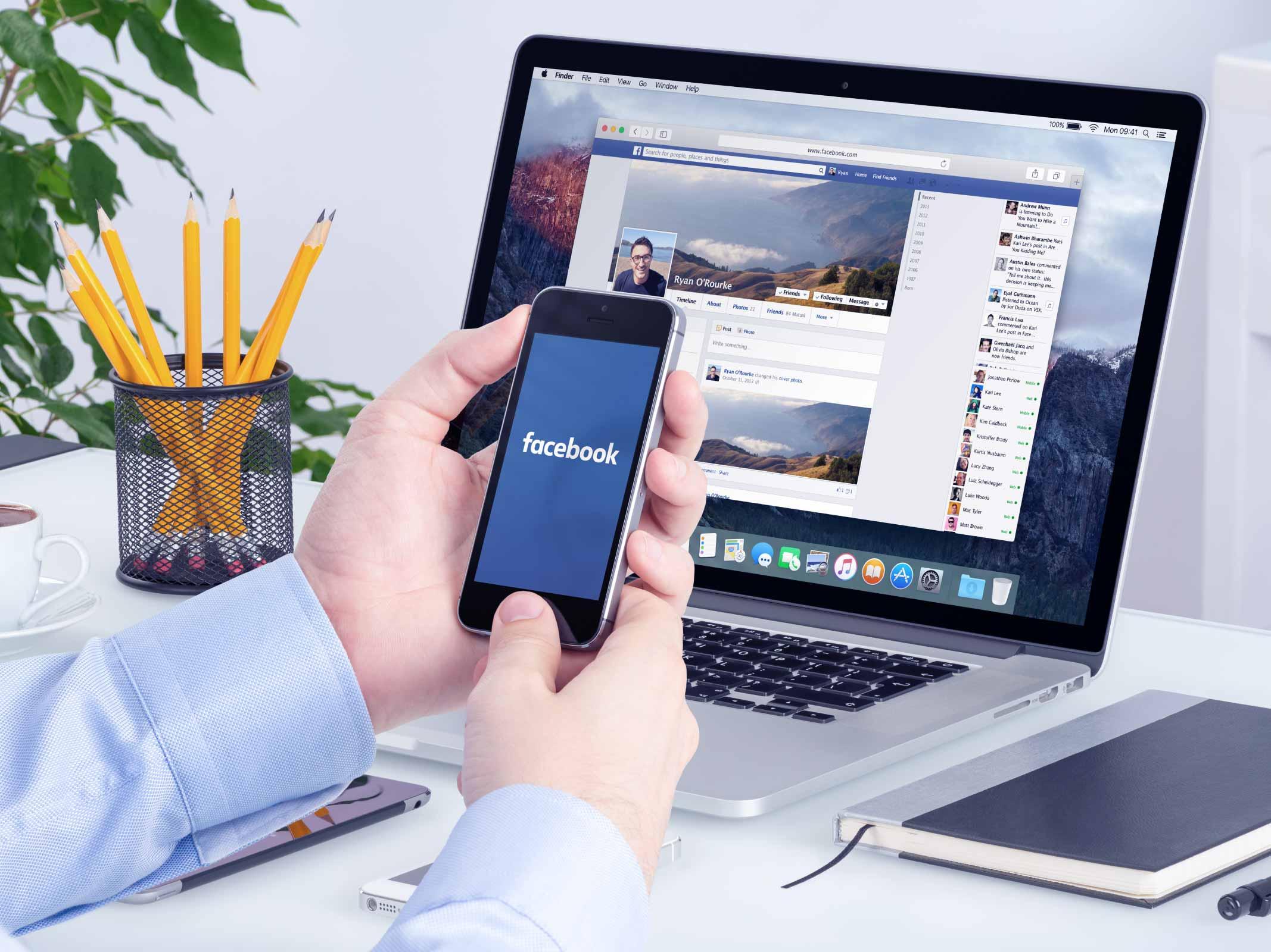 bureau avec une personne qui tient son smartphone allumé sur Facebook devant un ordinateur portable affichant également l'interface de Facebook
