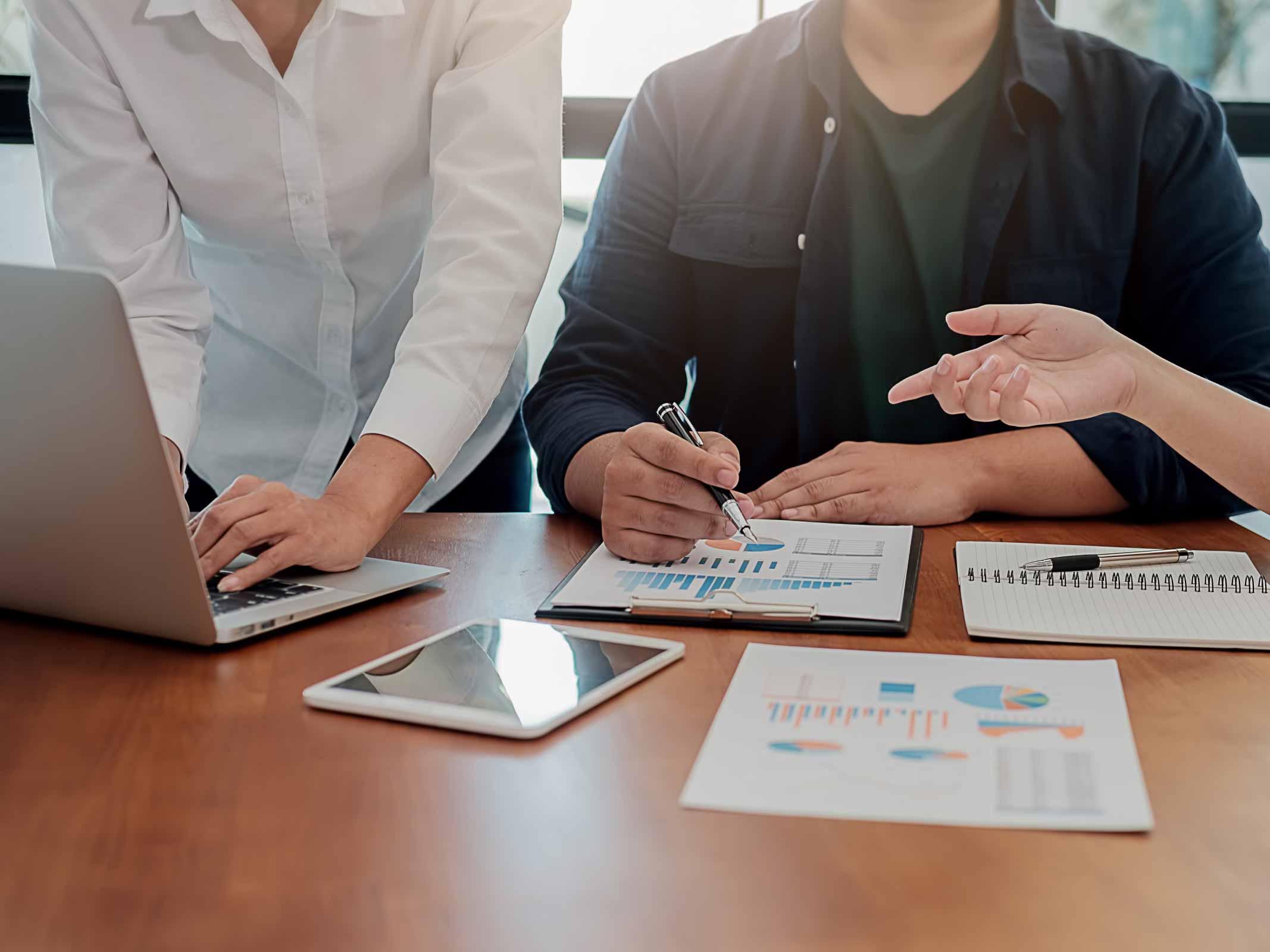 trois personnes travaillent autour d'une table avec des papiers contenant des graphiques, un ordinateur portable et une tablette tactile