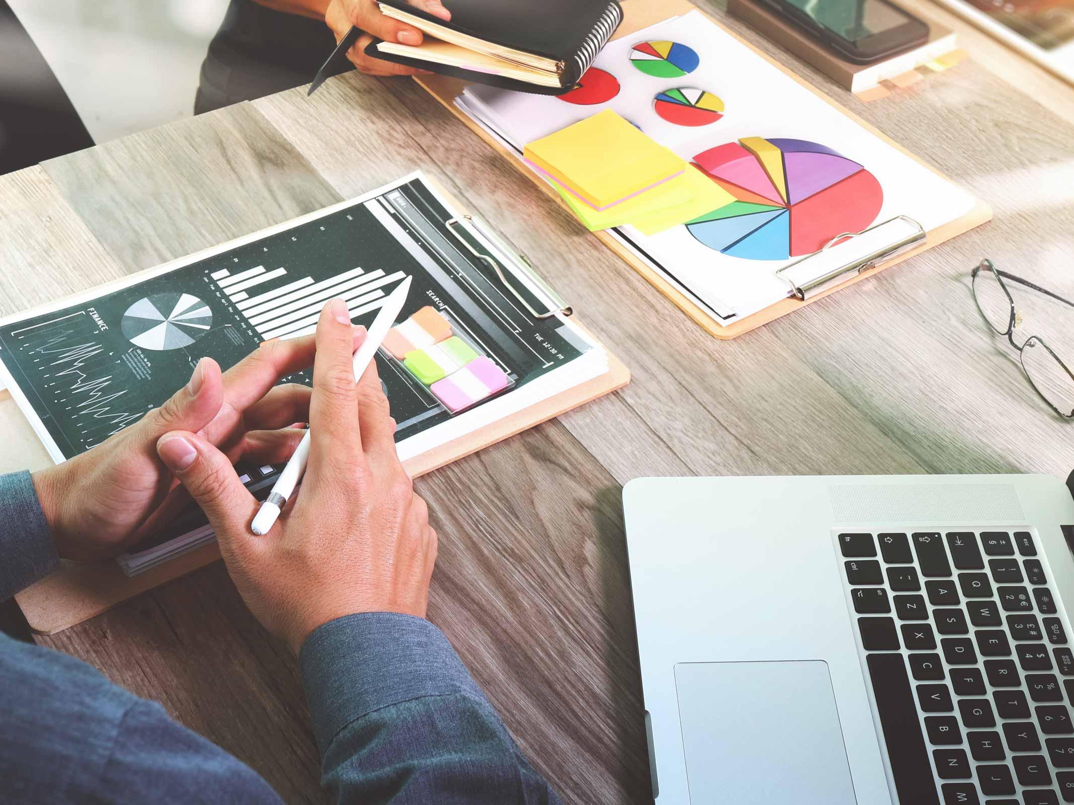 bureau avec ordinateur portable, papiers avec graphiques et lunettes
