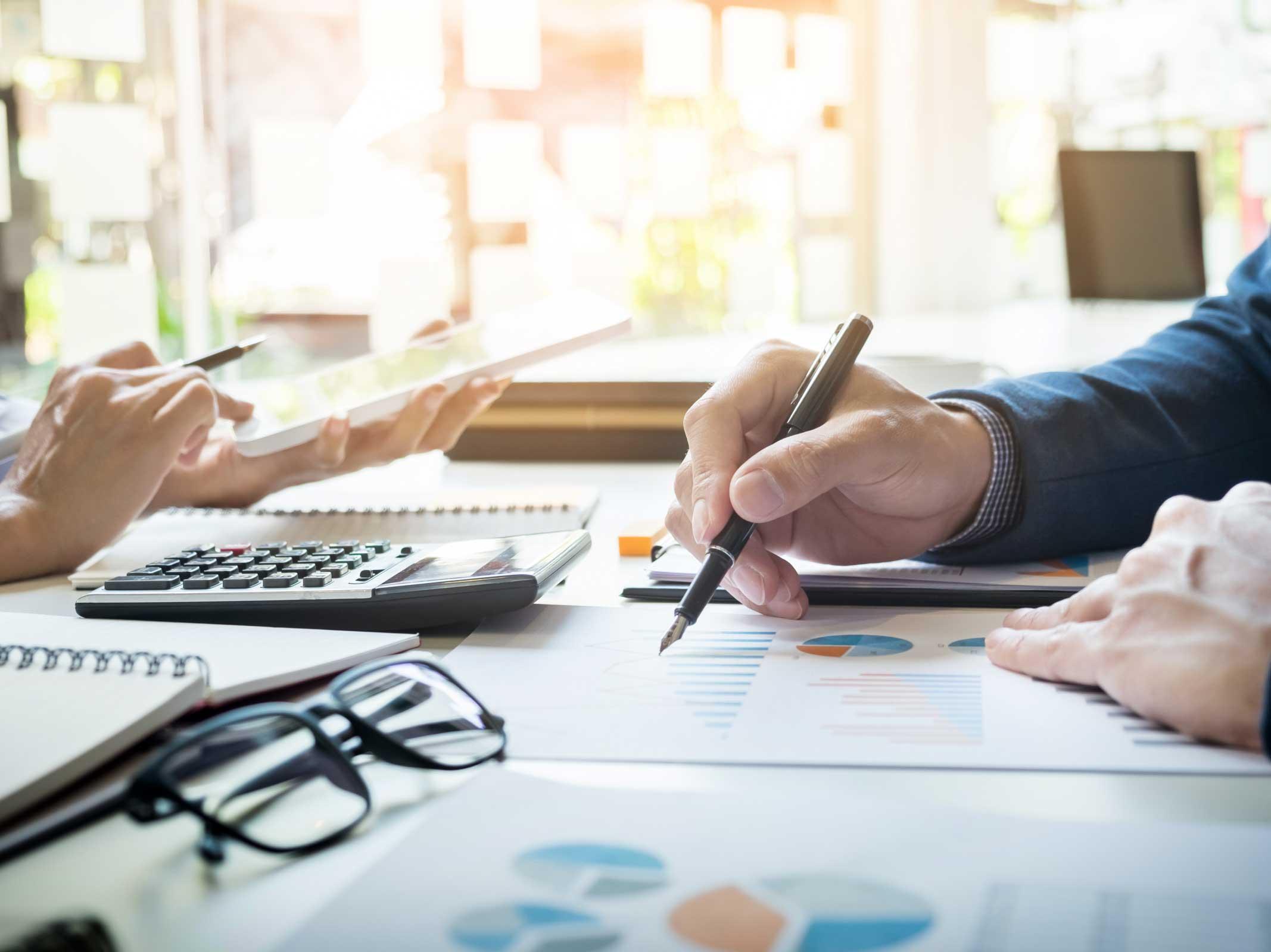 main qui écrit sur un bureau au dessus de graphiques stratégiques